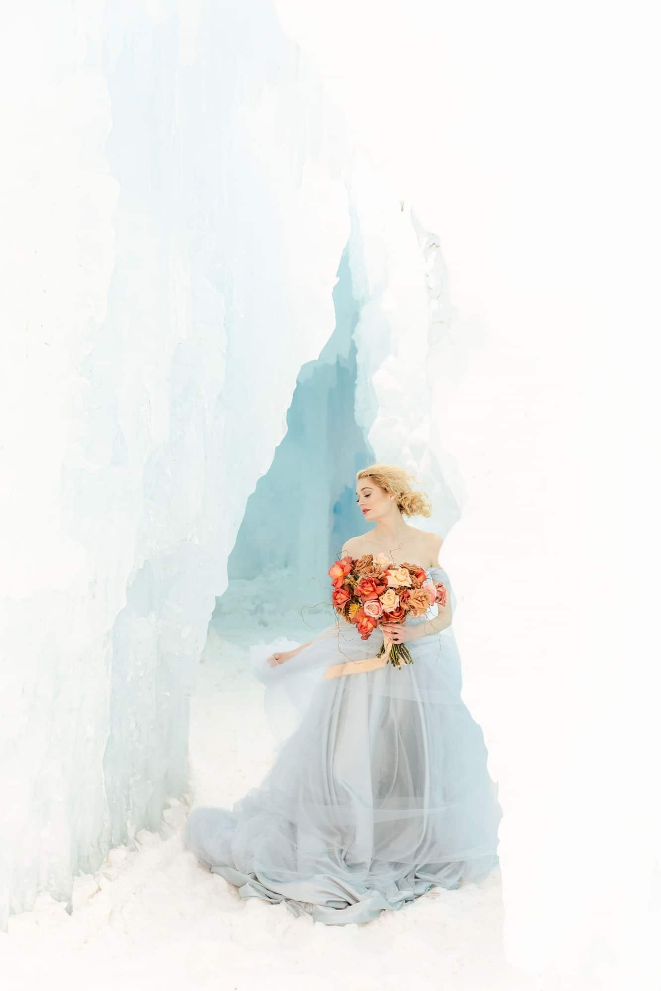beautiful bride walking out of an ice cave holding a coral and mustard bouquet