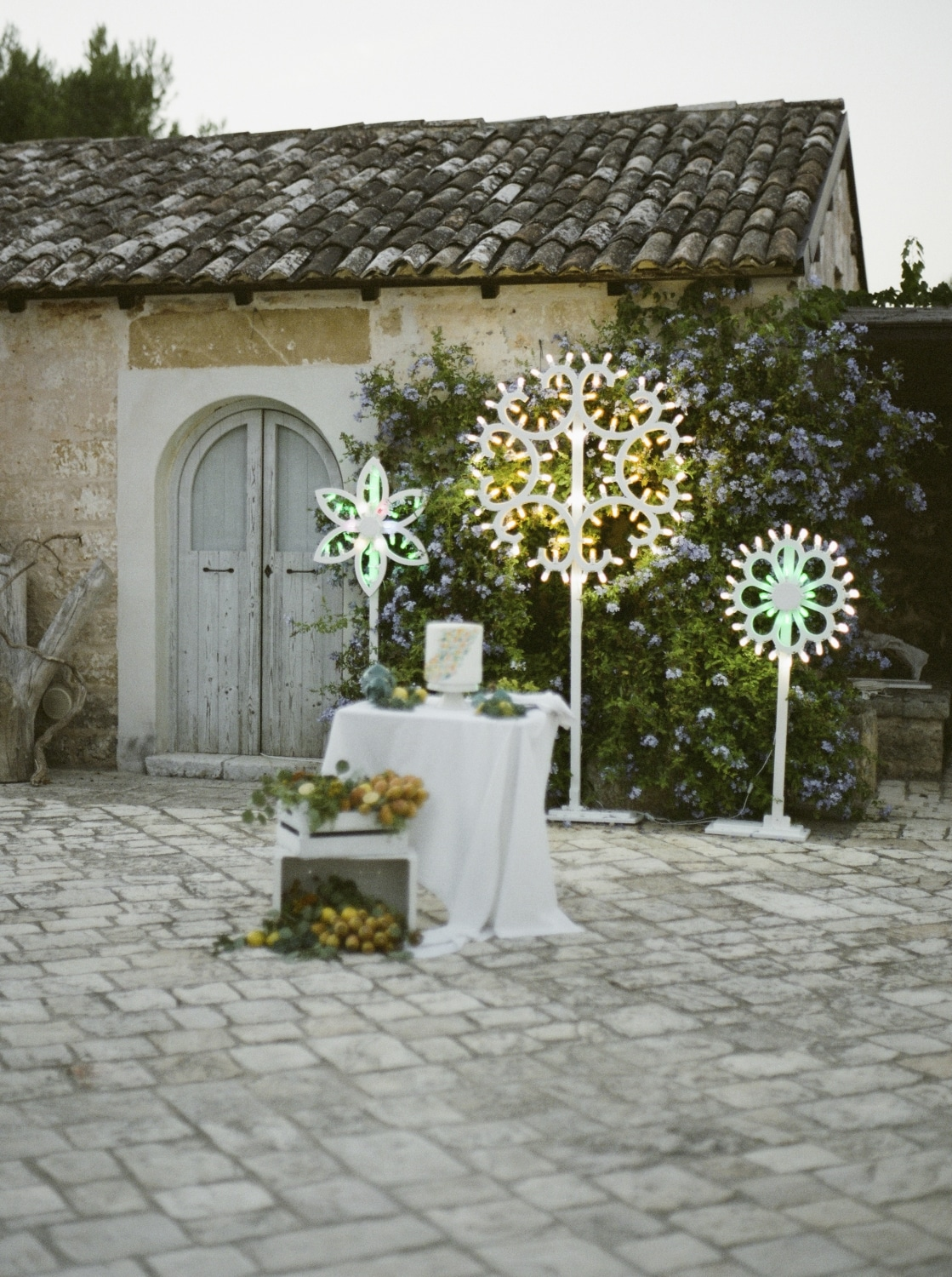 table setting in Apulia italy with lit star pendants behind table