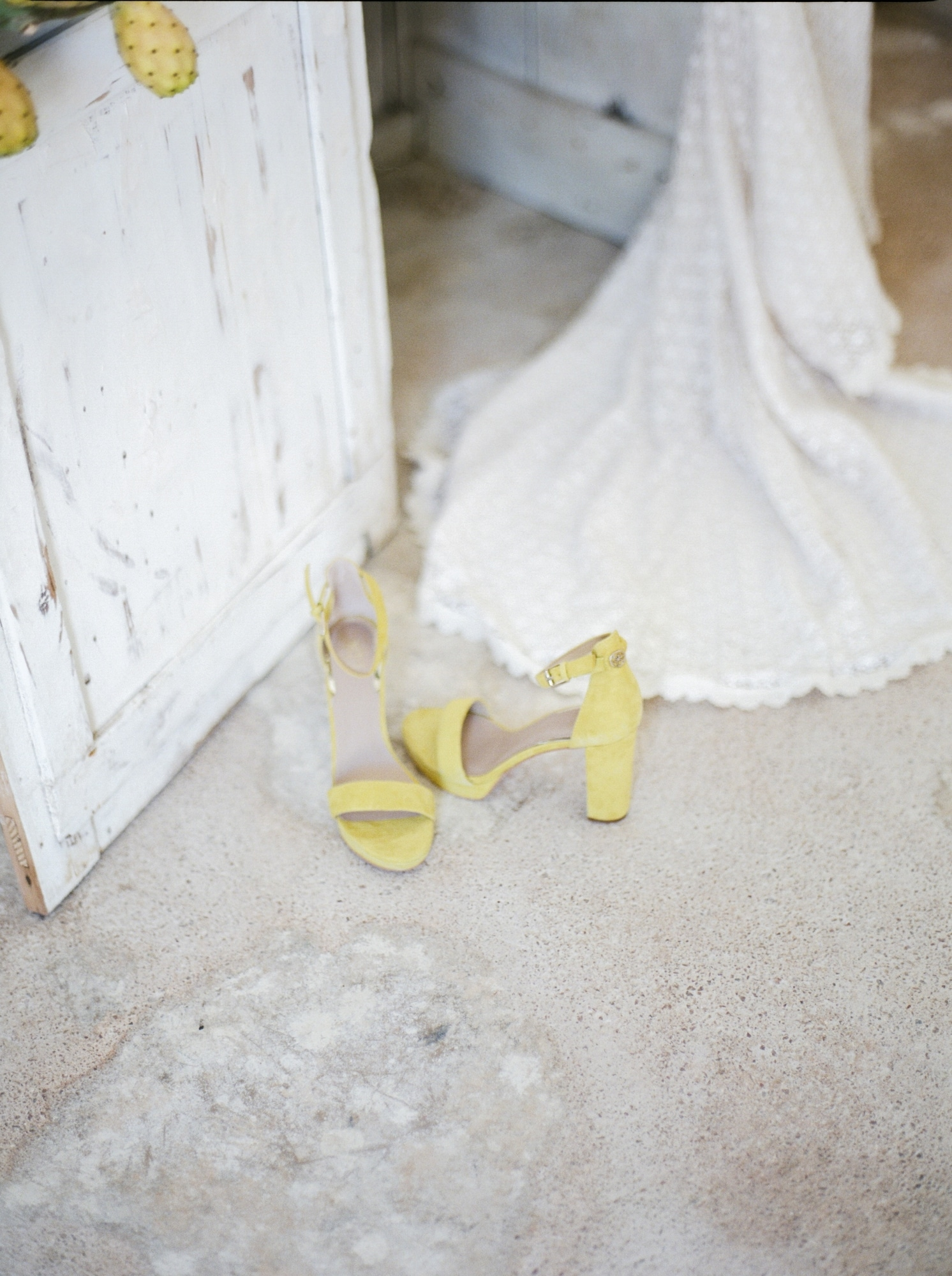 yellow wedged heel with bride's dress in the background