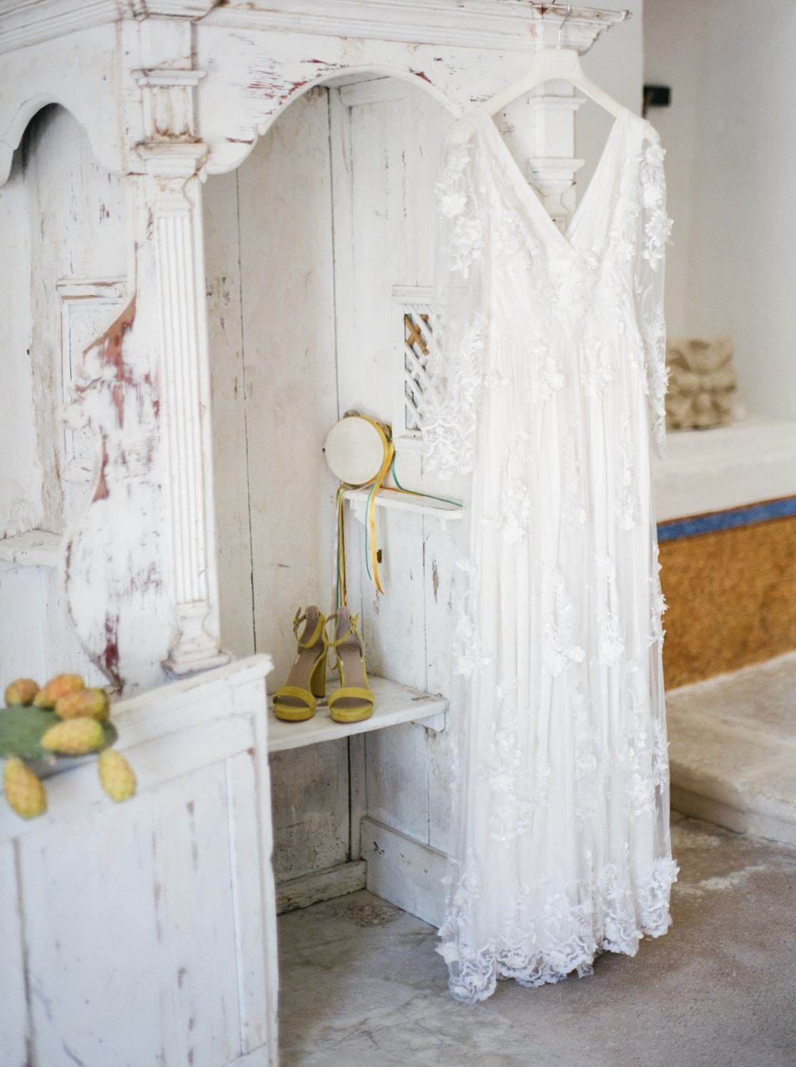 bride's shoes with gown on vintage white dresser in Italian wedding