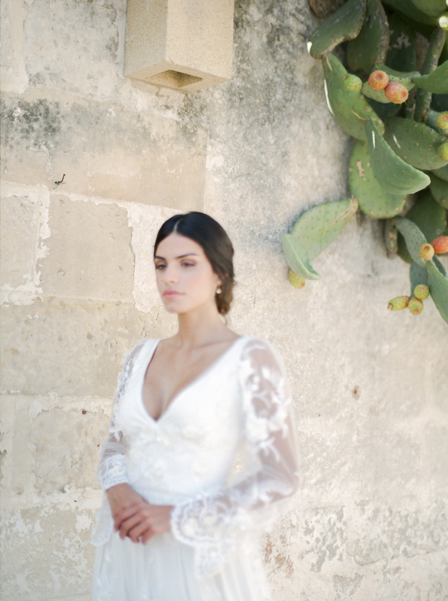 bride with low bun in hair and long sleeve dress in Apulia italy