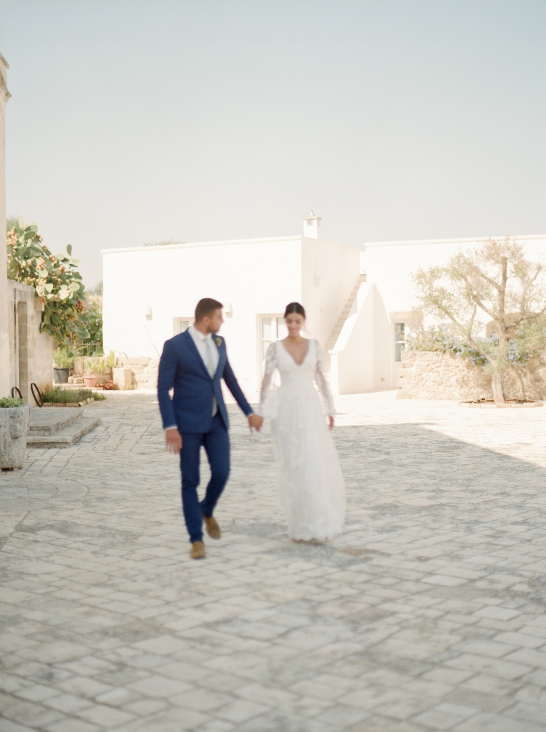bride and groom holding hands walking on cobblestone road