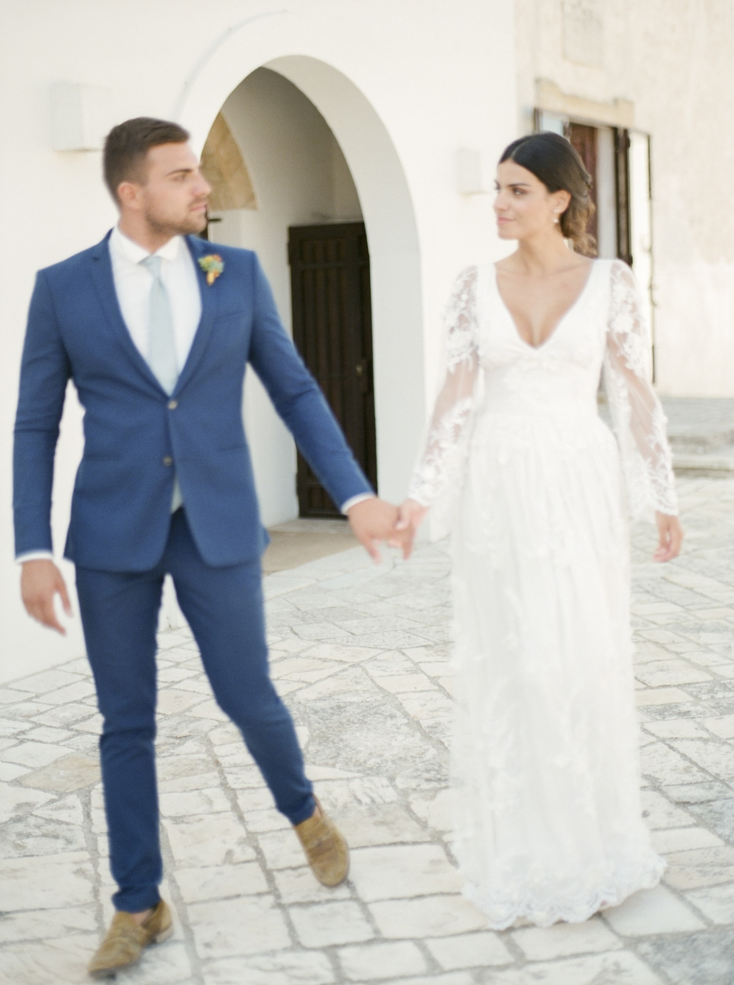 groom in navy suit and bride in all lace long sleeve fitted gown in Apulia Italian wedding